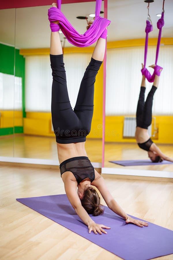 Ung härlig kvinna som gör flyg- yogaövning i purpurfärgad hängmatta i konditionklubba arkivfoto
