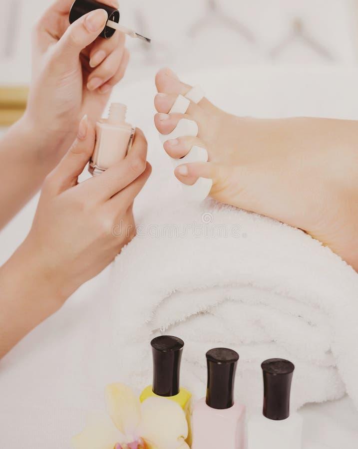 Ung härlig kvinna som gör pedikyr i den Spa salongen royaltyfri foto