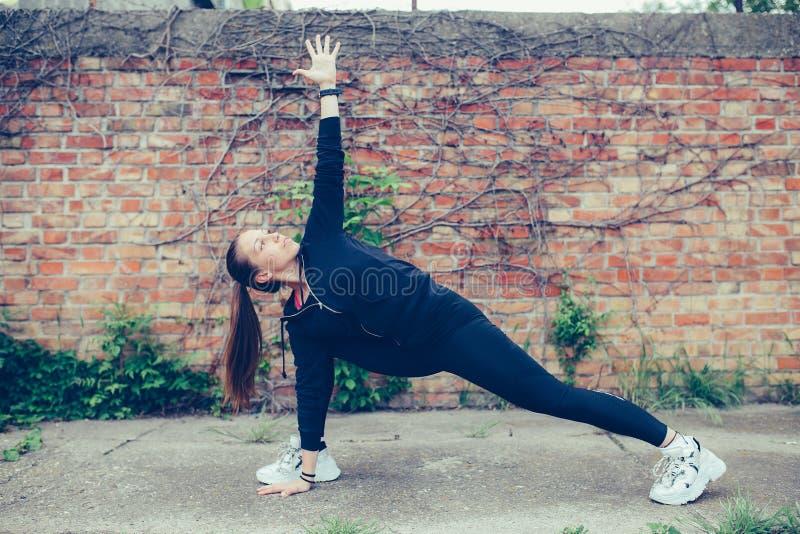 Ung härlig kvinna som gör sträcka övningar, tegelstenvägg i bakgrunden arkivfoton