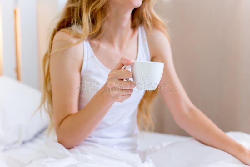 Ung härlig kvinna som har frukosten i underlag arkivfoton