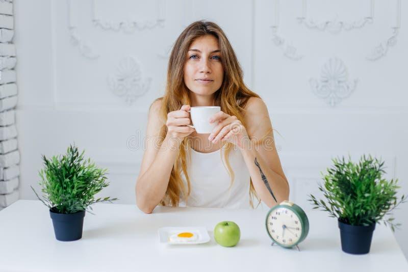 Ung härlig kvinna som har frukosten i underlag royaltyfria foton
