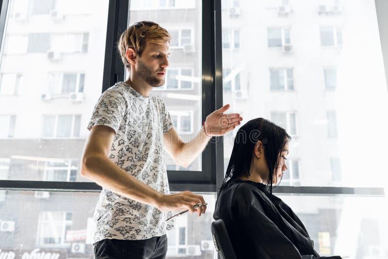 Ung härlig kvinna som har hennes hår att klippas på frisör`en s Ung manlig frisör som ler och gör frisyren till arkivfoto