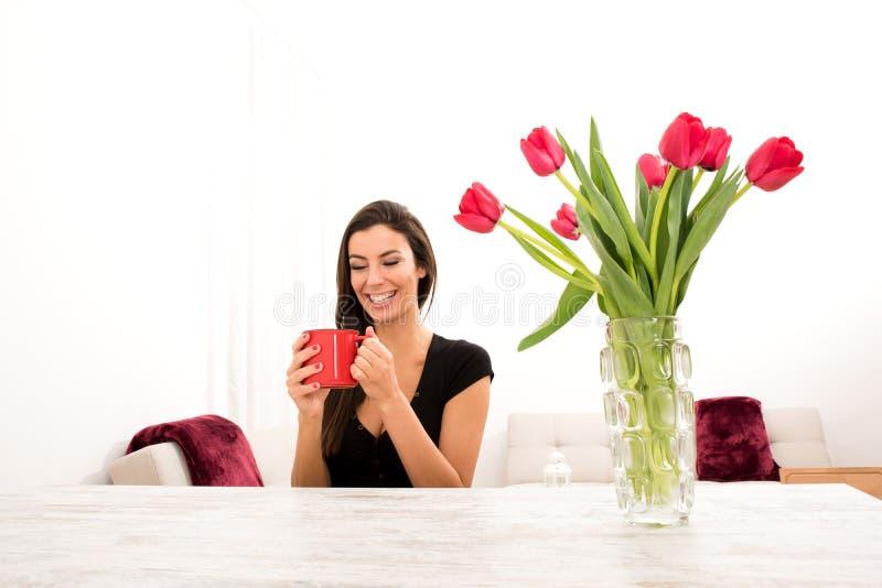 Ung härlig kvinna som hemma dricker kaffe arkivbilder