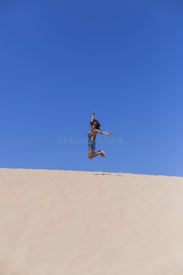 ung härlig kvinna som hoppar på dyerna i Portugal Sommartid, gyckel och feriebegrepp royaltyfria foton