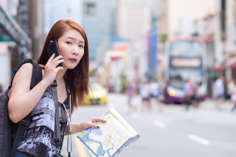 Ung härlig kvinna som kallar den offentliga taxien vid telefonen royaltyfri fotografi