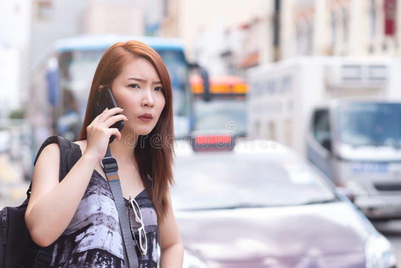 Ung härlig kvinna som kallar den offentliga taxien vid telefonen royaltyfria foton