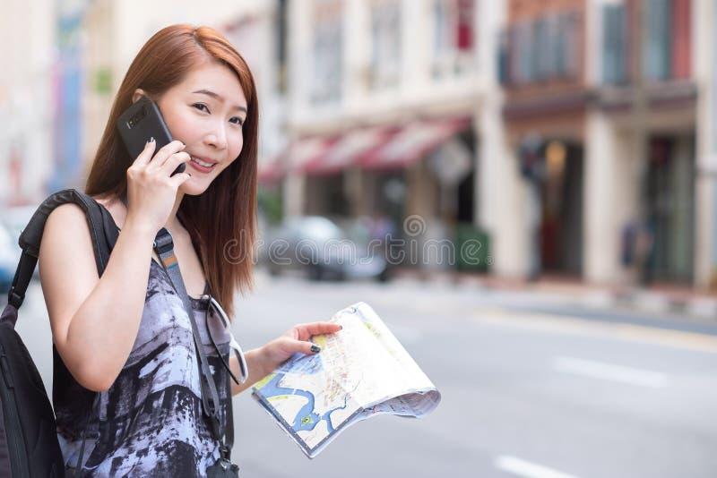 Ung härlig kvinna som kallar den offentliga taxien vid telefonen royaltyfria bilder