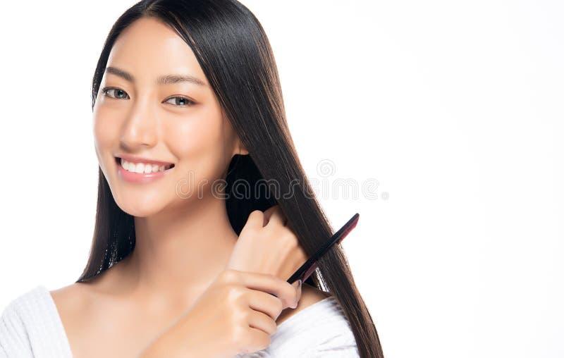 Ung härlig kvinna som kammar hennes hår på vit bakgrund arkivfoto