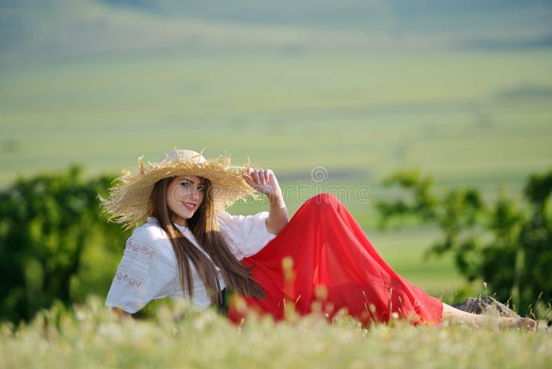 Ung härlig kvinna som kopplar av på fält i summe royaltyfri foto