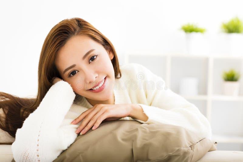 Ung härlig kvinna som kopplar av på soffan royaltyfri bild