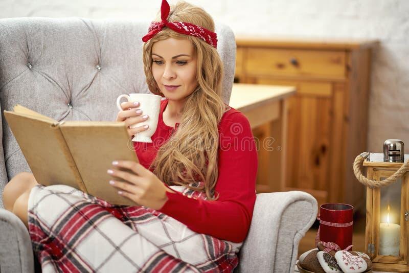 Ung härlig kvinna som läser en bok i en fåtölj med filten och te under jultid arkivfoton