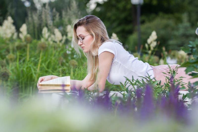 Ung härlig kvinna som läser en bok som ligger på bänken runt om gräset och blommorna på sommardagen royaltyfri foto