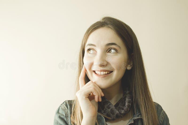 Ung härlig kvinna som ler och tänker över grå bakgrund arkivbilder