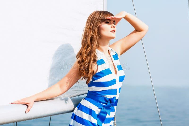 Ung härlig kvinna som poserar på yachten i solig dag arkivfoton