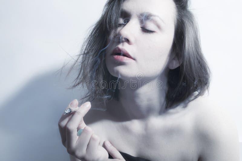 ung härlig kvinna som röker cigaretten arkivbild