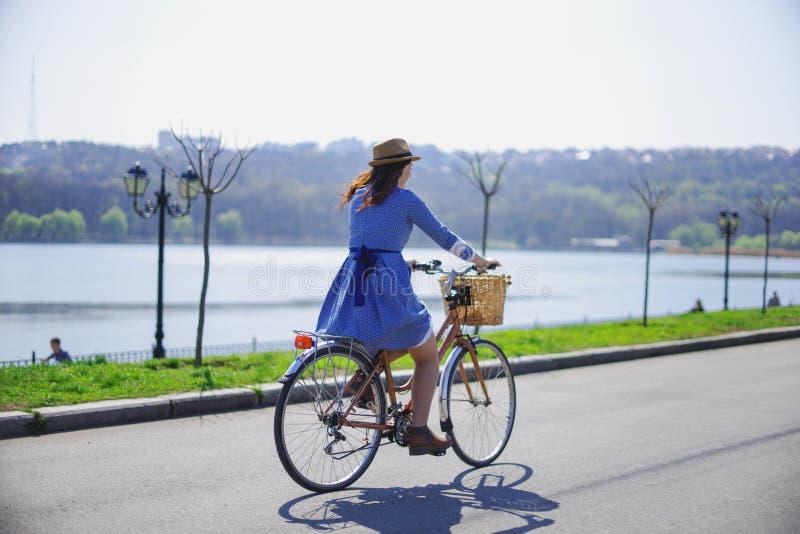 Ung härlig kvinna som rider en cykel i en parkera Aktivt folk arkivbild