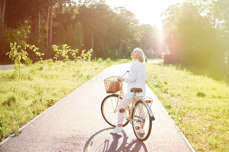 Ung härlig kvinna som rider en cykel i en parkera Aktivt folk Koppla av utomhus royaltyfri foto