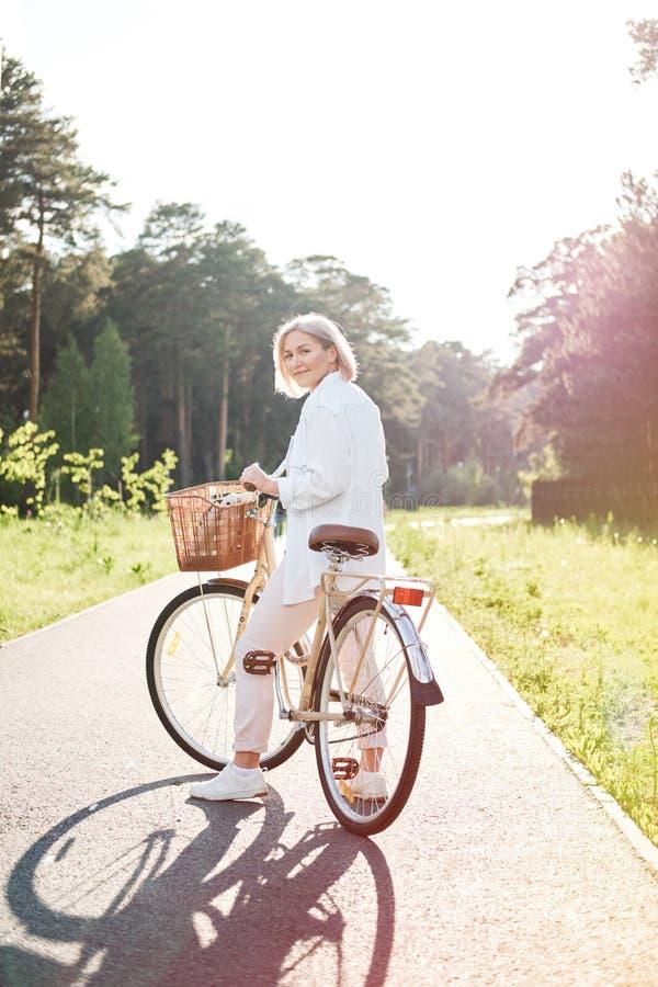 Ung härlig kvinna som rider en cykel i en parkera Aktivt folk Koppla av utomhus royaltyfri fotografi