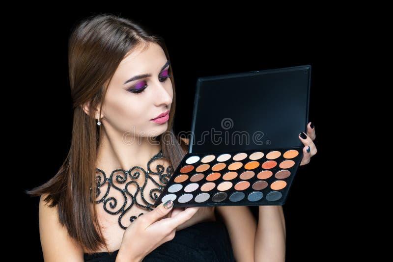 Ung härlig kvinna som rymmer orange skuggor för plast- palettbrunt fotografering för bildbyråer