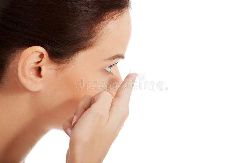 Ung härlig kvinna som sätter kontaktlinsen. arkivfoto