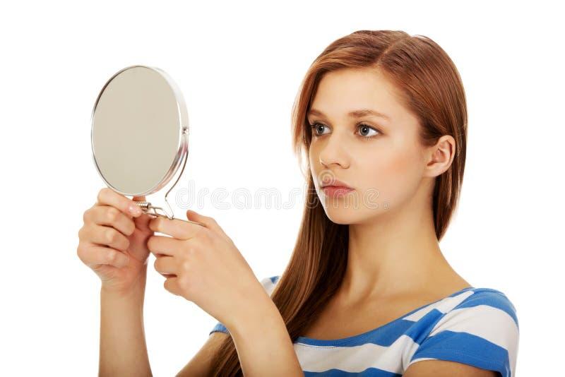 Ung härlig kvinna som ser i en spegel arkivfoton