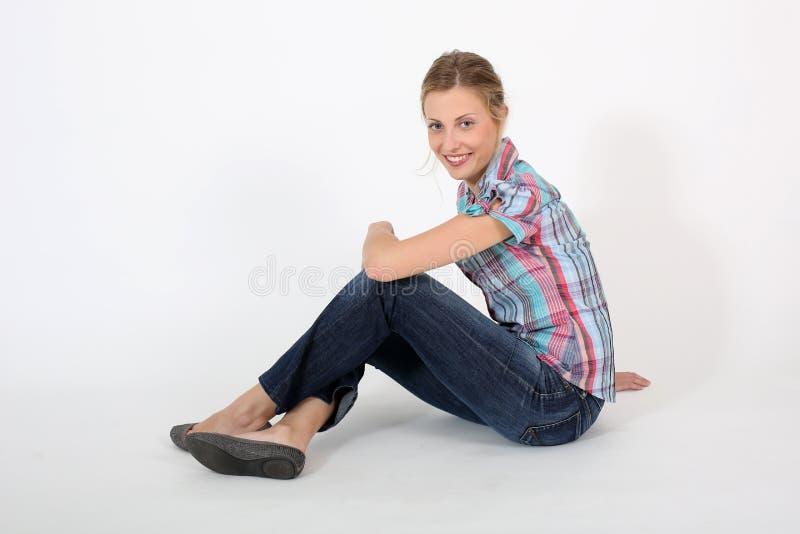 Ung härlig kvinna som sitter ner isolerat arkivfoto