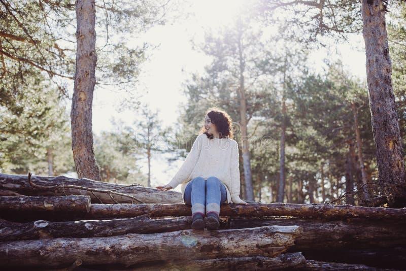 Ung härlig kvinna som sitter på stammar och att le för trä tillbaka lampa Det fria och livsstil royaltyfri bild
