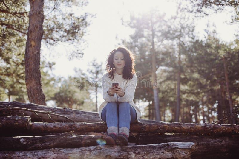 Ung härlig kvinna som sitter på trästammar och använder mobiltelefonen tillbaka lampa Det fria och livsstil fotografering för bildbyråer