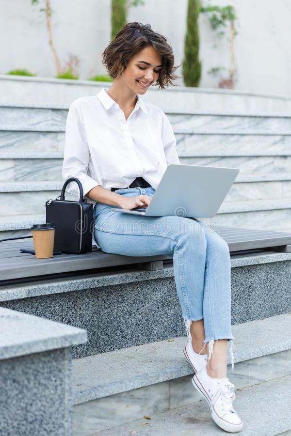Ung härlig kvinna som sitter utomhus genom att använda bärbar datordatoren royaltyfria bilder