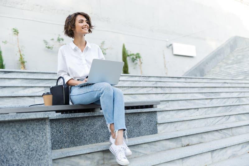 Ung härlig kvinna som sitter utomhus genom att använda bärbar datordatoren royaltyfria foton