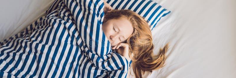 Ung härlig kvinna som sover i hennes säng och kopplar av i morgonBANRET, långt format royaltyfria foton