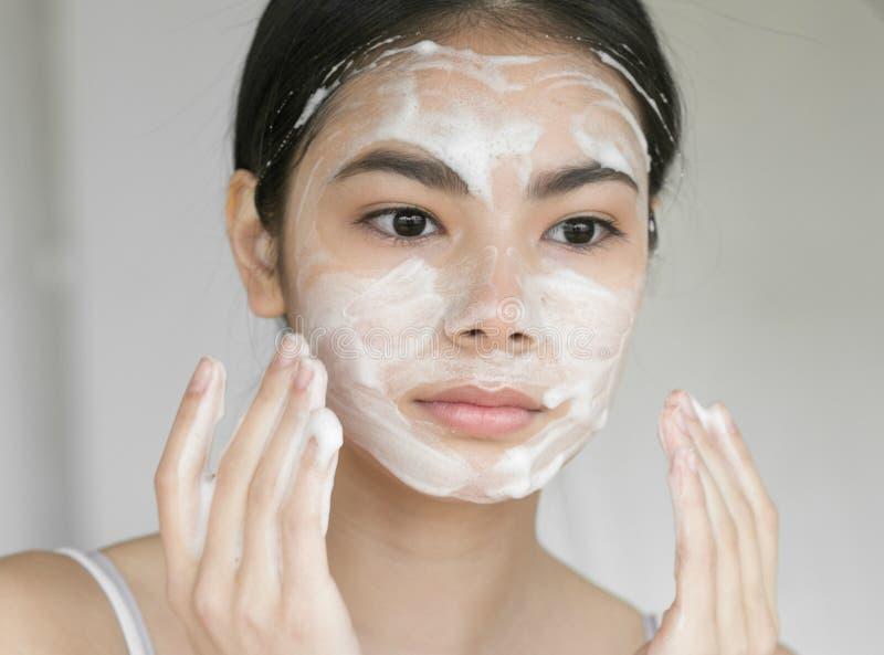 Ung härlig kvinna som tvättar hennes framsida med tvål fotografering för bildbyråer