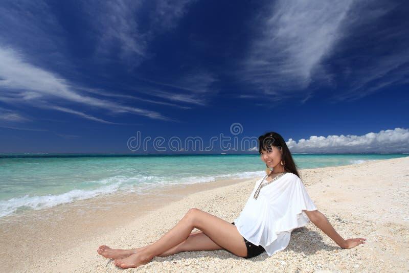 Ung härlig kvinna som tycker om solen på stranden royaltyfri foto