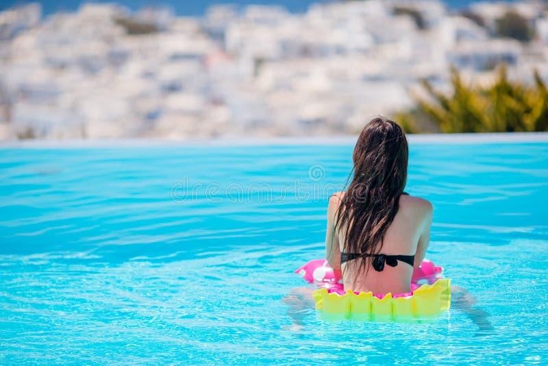 Ung härlig kvinna som tycker om sommarsemester i utomhus- simbassäng arkivbild