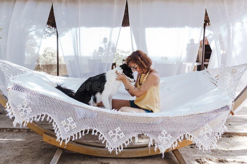 Ung härlig kvinna som utomhus sitter på hängmattan med hennes border collie hund Gyckel- och sommarlivsstil fotografering för bildbyråer