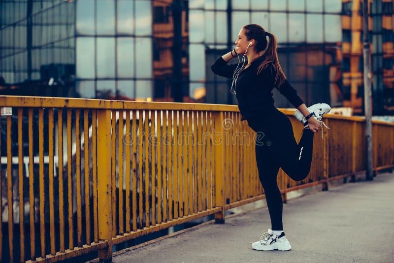 Ung härlig kvinna som värmer upp på flodbron royaltyfri bild