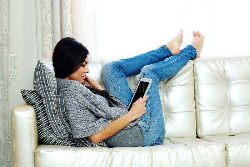 Ung härlig kvinna som vilar på en soffa med minnestavladatoren fotografering för bildbyråer
