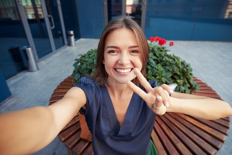 Ung härlig kvinna som visar tecken V, medan göra en selfie arkivbild