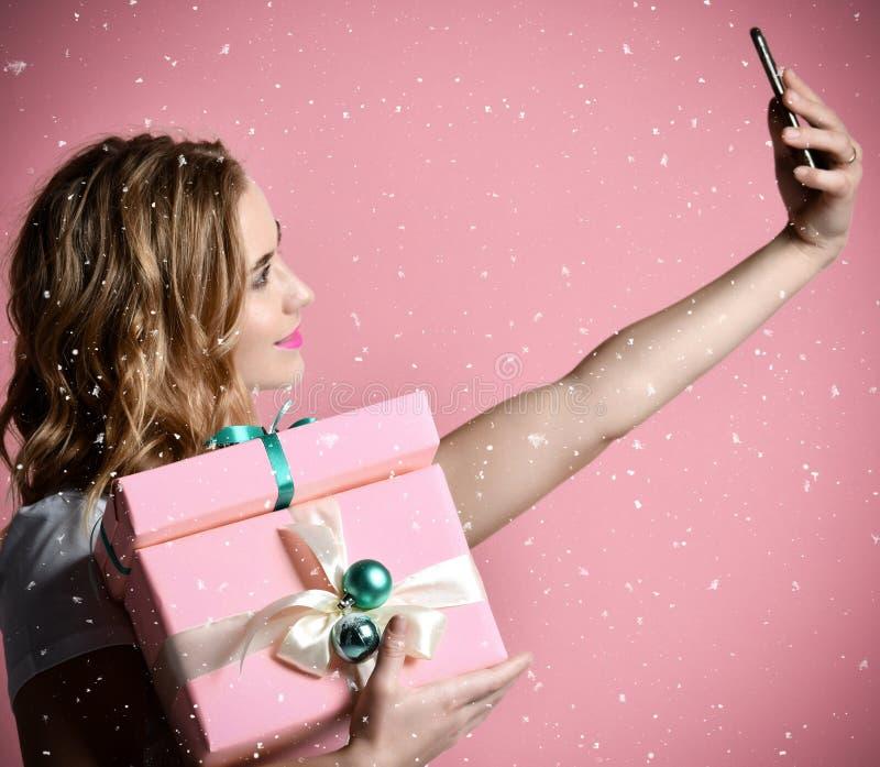 Ung härlig kvinnahålljul framlägger gåvor som ler och att göra selfiefotoet med hennes mobiltelefonmobil royaltyfria foton