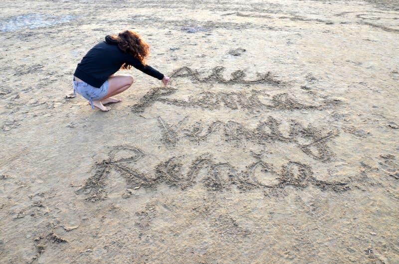 Ung härlig kvinnahandstil in i en sand på stranden fotografering för bildbyråer