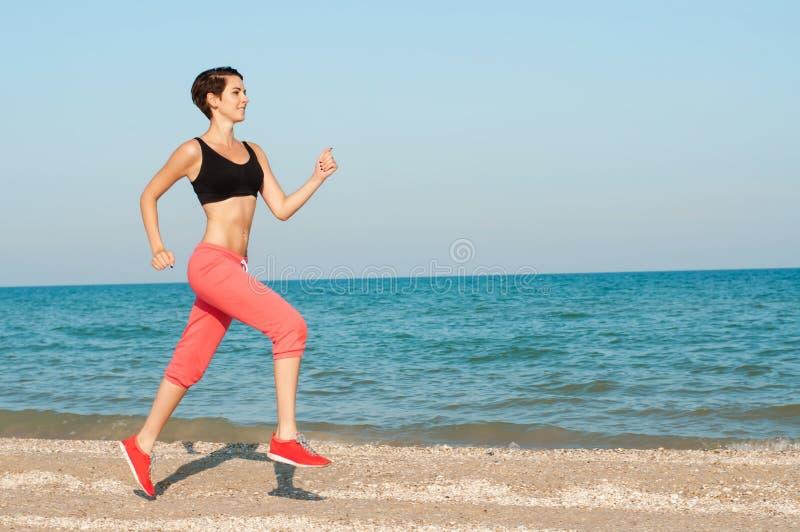 Ung härlig kvinnaidrottsman nenspring på stranden arkivfoto