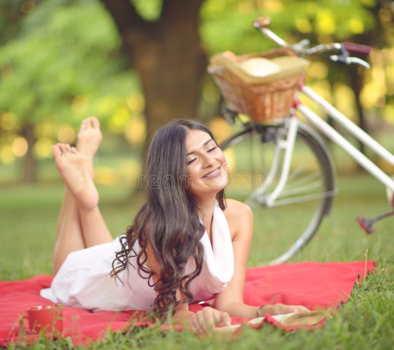 Ung härlig kvinnaläsebok utomhus in att parkera på en solig dag fotografering för bildbyråer