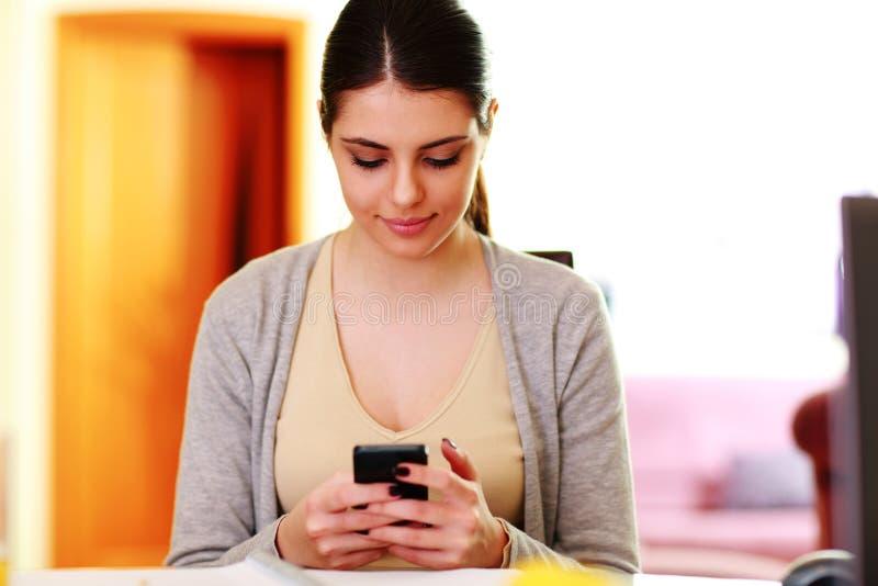 Ung härlig kvinnamaskinskrivning på smartphonen royaltyfri foto