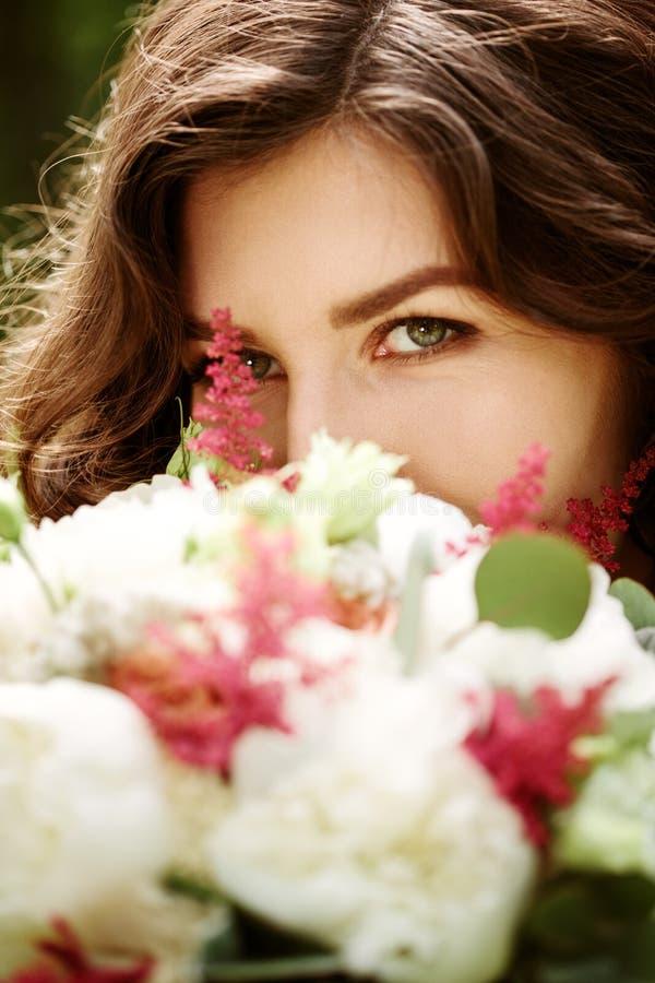 Ung härlig kvinnanärbild bak blommor royaltyfri fotografi