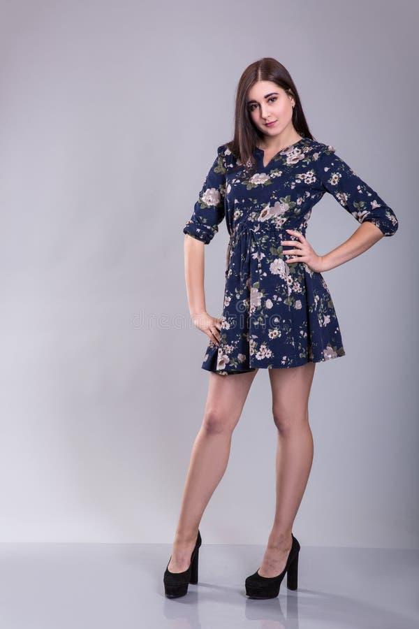 Ung härlig kvinnlig modell i färgrik klänning på grå bakgrund arkivfoton