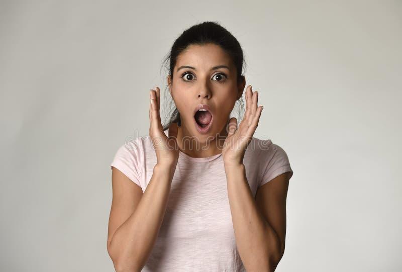 Ung härlig latinamerikan förvånad kvinna som förbluffas i chock och överraskning med öppnat stort för mun fotografering för bildbyråer
