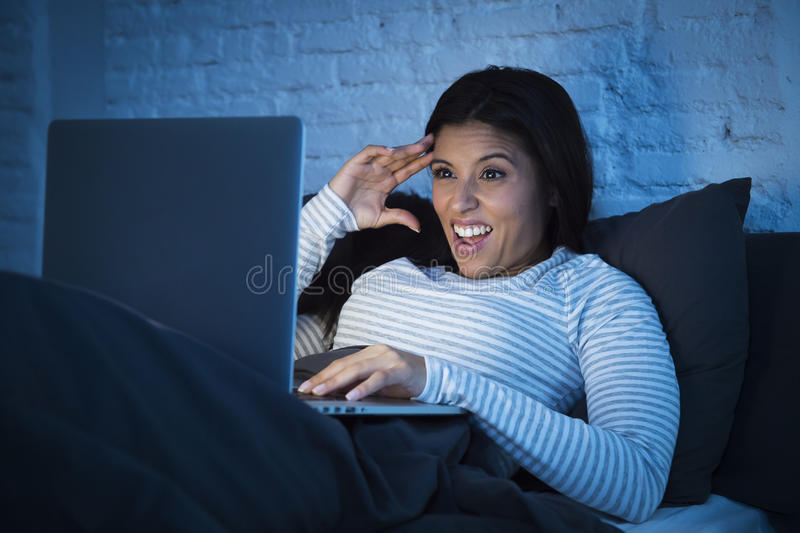 Ung härlig latinamerikansk kvinna på att skratta för säng som hemma är lyckligt på bärbar datordatoren på natten royaltyfria foton