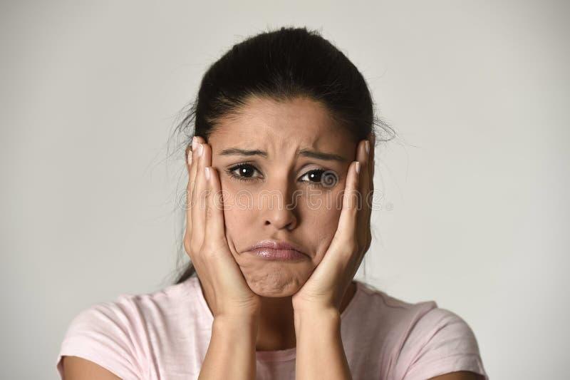 Ung härlig latinamerikansk ledsen kvinna som är allvarlig och som är bekymrad i bekymrat deprimerat ansiktsuttryck fotografering för bildbyråer