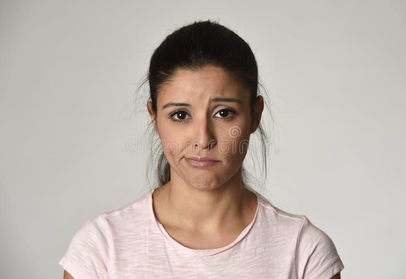 Ung härlig latinamerikansk ledsen kvinna som är allvarlig och som är bekymrad i bekymrat deprimerat ansiktsuttryck arkivfoto