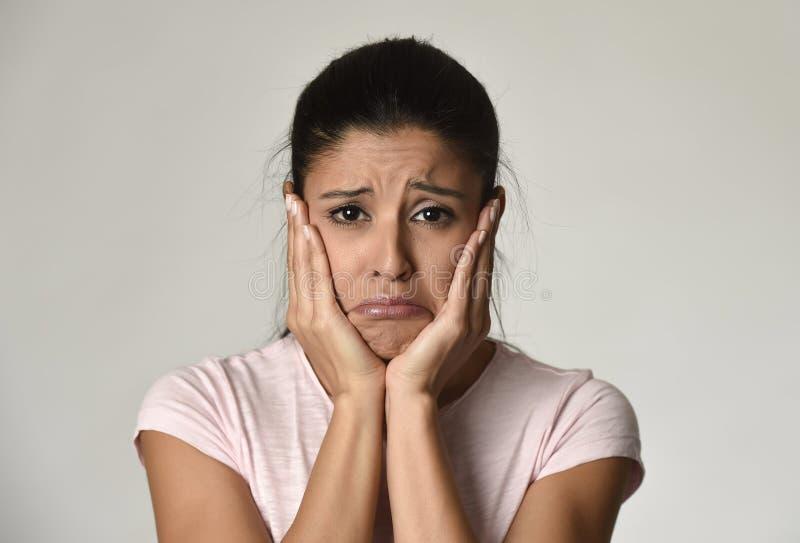 Ung härlig latinamerikansk ledsen kvinna som är allvarlig och som är bekymrad i bekymrat deprimerat ansiktsuttryck royaltyfria bilder